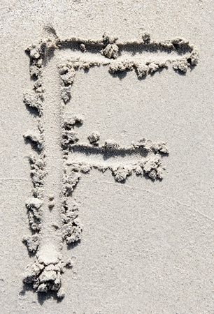 sand writing: The letter F of the alphabet writing on the sand beach
