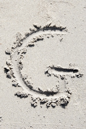 sand writing: The letter G of the alphabet writing on the sand beach