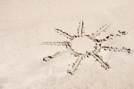 sand writing: The  sun  drawing  in the sand on a beach Stock Photo