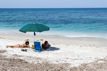 A couple relaxing on a beach under colorful umbrellas photo