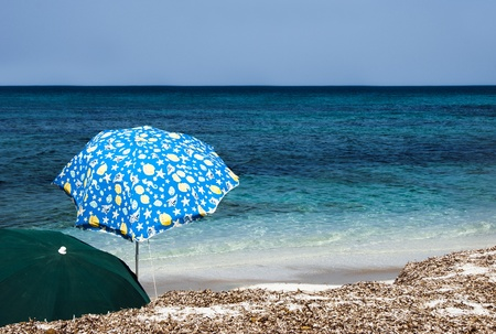 deserted: Beach umbrellas on a sunny day - sea in background