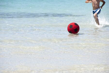 A boy playing beach ball in the sea photo