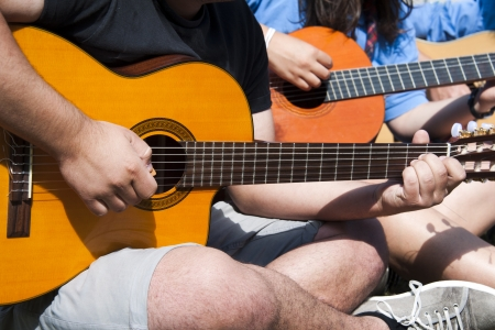 A grouo of young people playing guitar together