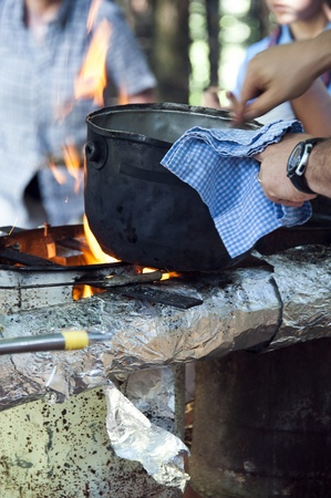 cooking food in pot on fire at camping place photo