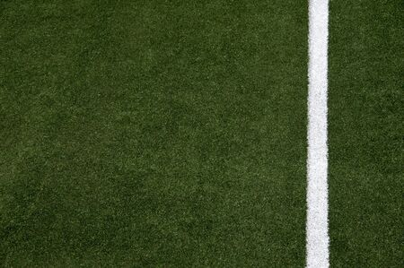 White stripes on the green soccer field from top view photo