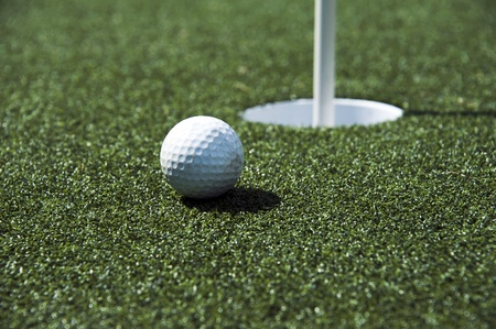 A golf ball sits near the hole on the putting green photo