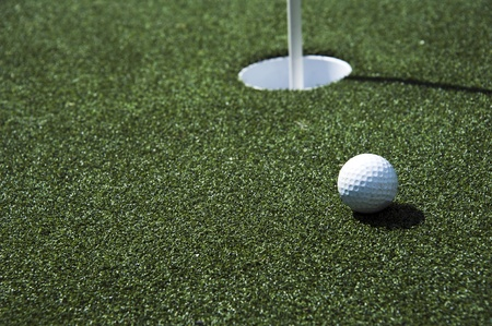 driving range: A golf ball sits near the hole on the putting green