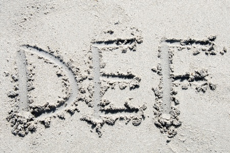 sand writing: The letters D, E  and F of the alphabet writing on the sand beach Stock Photo
