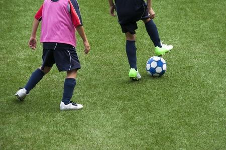 pasto sintetico: Los niños pequeños jugando el juego de fútbol