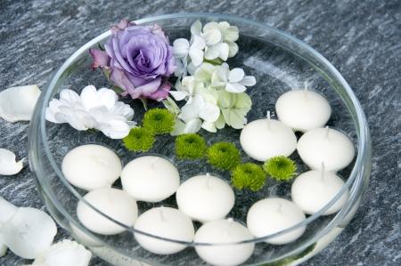 Úszó gyertyák és virágok dekoráció egy kerti party