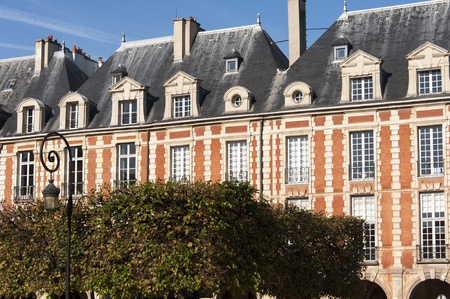 Beautiful buildings of Place des Vosges, square in Paris, France,