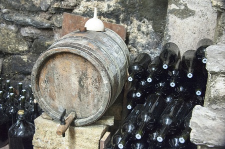 oak barrel: Old wine barrels and bottles in a cellar