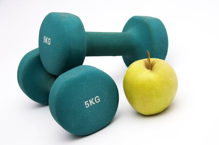 Fitness  concept - dumbbells, apple and measure tape photo
