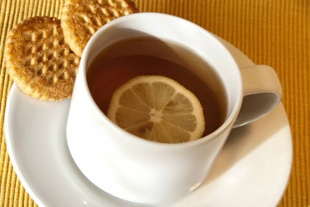 time table: tea time  a cup of tea with biscuits and lemon Stock Photo
