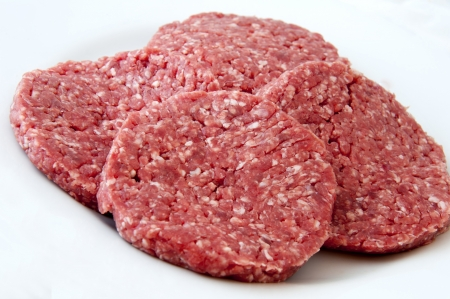 Raw beef burgers against white background photo