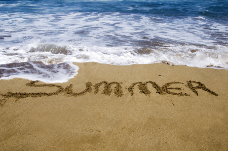 The word summer written in the sand on a beach photo
