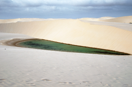 Lagoa azul in desert white sand dunes of the Lencois Maranheses National Park in brazil photo