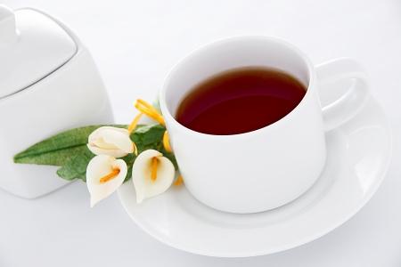 yellow tea pot: Tea time - a cup of tea with sugar pot and flowers