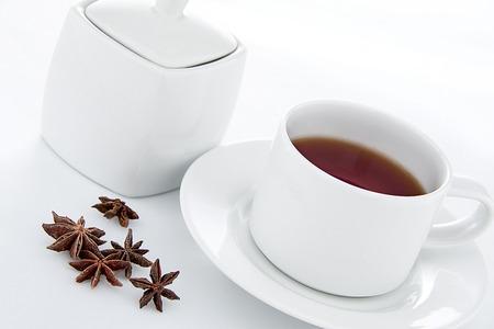 yellow tea pot: Tea time - a cup of tea with sugar pot and star anise Stock Photo