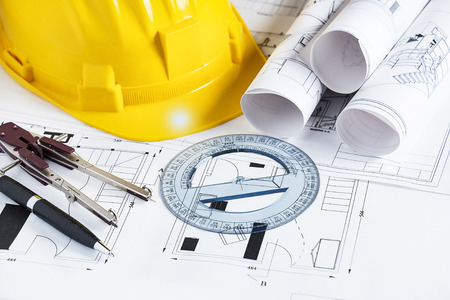 Engineer worplace with blueprints, compass, pen, protractor  and safety helmet Stock Photo