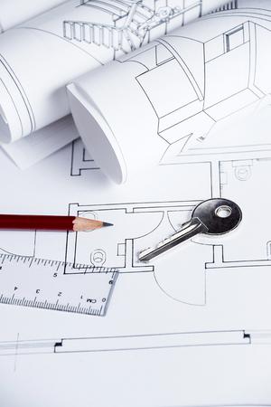 Architect worplace with blueprints and house key photo