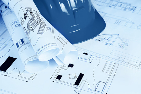 Engineer worplace with blueprints  and safety helmet in blue tone Stock Photo