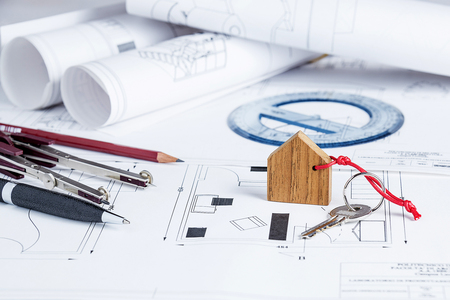 Architect worplace with blueprints, tools and house key
