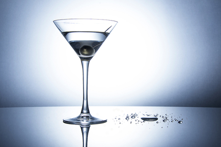 martini splash: An Olive Martini Cocktail with drops on the table - blue tone Stock Photo