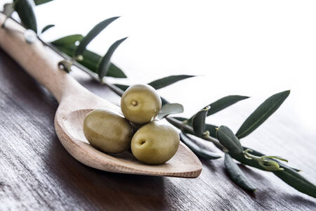 pickled green olives in a wooden spoon photo