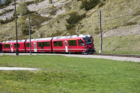 Swiss red train between alpine mountains photo