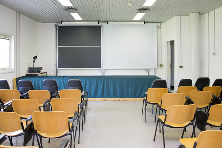 An empty classroom with wooden chairs