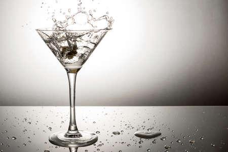 Olive splashing on a martini cocktail photo