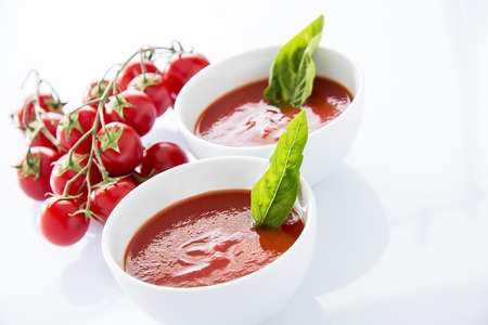 Tomato juice bowls with cherry tomatoes on white background photo