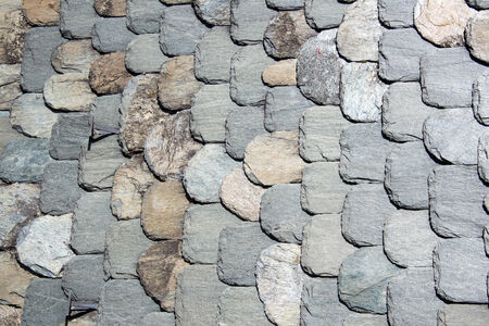 Stone tiles of slate-roof rural house as background photo