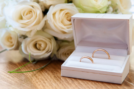 Wedding rings with a bouquet of white roses photo