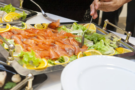 person appetizer: Catering at wedding reception - people choosing buffet food appetizers