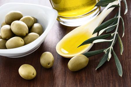 aceite oliva: Aceite de oliva y aceitunas rama sobre la mesa de madera