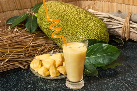 Jackfruit juice in een glas. Verse zoete jackfruitplakken op een glasplaat. Exotische rijpe jackfruit klaar voor eten. Zoete jackfruitcocktail. Organisch fruitconcept. Tropisch fruit. Selectieve aandacht.