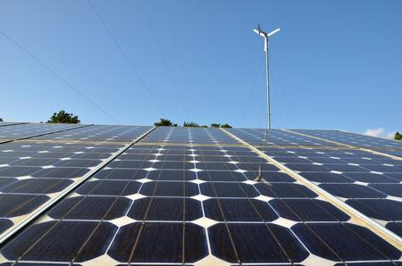 Solar panels and wind turbine against blue sky photo