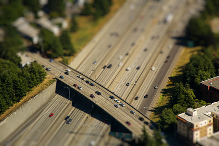tilt: Tilt shift detail of bridge crossing interstate highway with cars in the middle of city