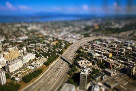 tilt: Tilt shift photo of busy interstate highway with cars during sunny day