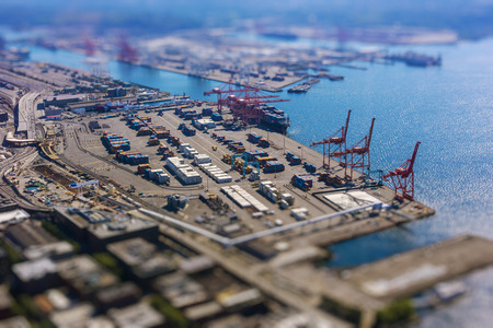 tilt: Tilt shift of shipping port with containers and loading transport ship with cargo