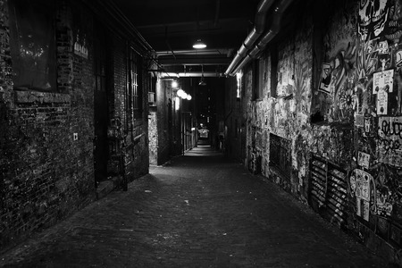 Black and white photo of darkness in a old grunge dirty street in the middle of night photo