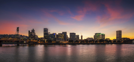 Portland, Oregon city skyline panorama with Hawthorne bridge. Colorful twilight sunset with dramatic sky and light reflection on the Willamette river. photo
