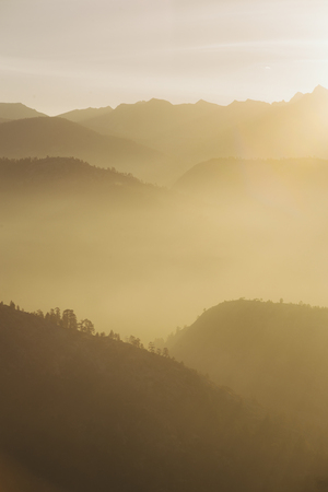 opacity: Mountain hills in Yosemite seen as a multiple layers of atmospheric perspective made from vaporizing dew which makes different opacity in bright morning sunrise