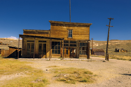 Crooked abandoned building of old western saloon and shop in Bodie Ghost Town