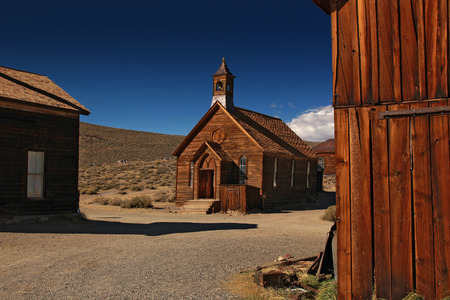 old mining building: Wooden church in ghost town Bodie with blues sky