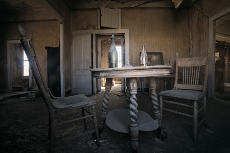 ghost town: Interior of abandoned building with two old chairs, table and bottle on it in Bodie Ghost Town