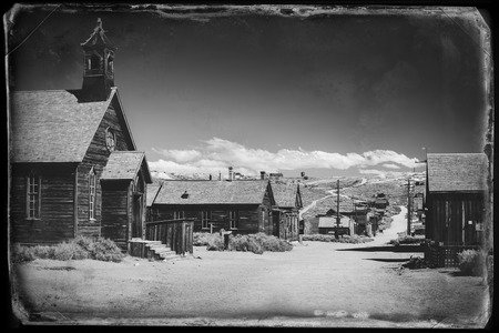 gold rush: Vintage black and white old looking photo of empty streets of abandoned ghost town Bodie in California, USA in the middle of a day. Stock Photo