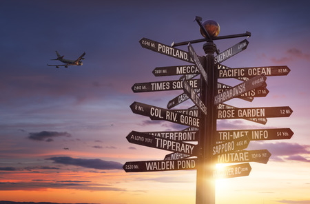 Travel the World! World Landmarks Signpost with sun and colorful cloudy sky in the background and free copy space for your text